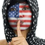 muslim with us flag and finger raised to her lips