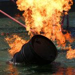 Barrel of oil on fire floating in water