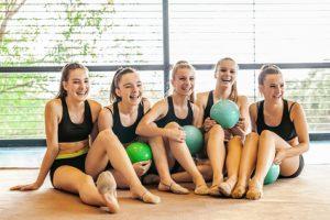 Teenage Girls Practising Rhythmic Gymnastics in the Gym